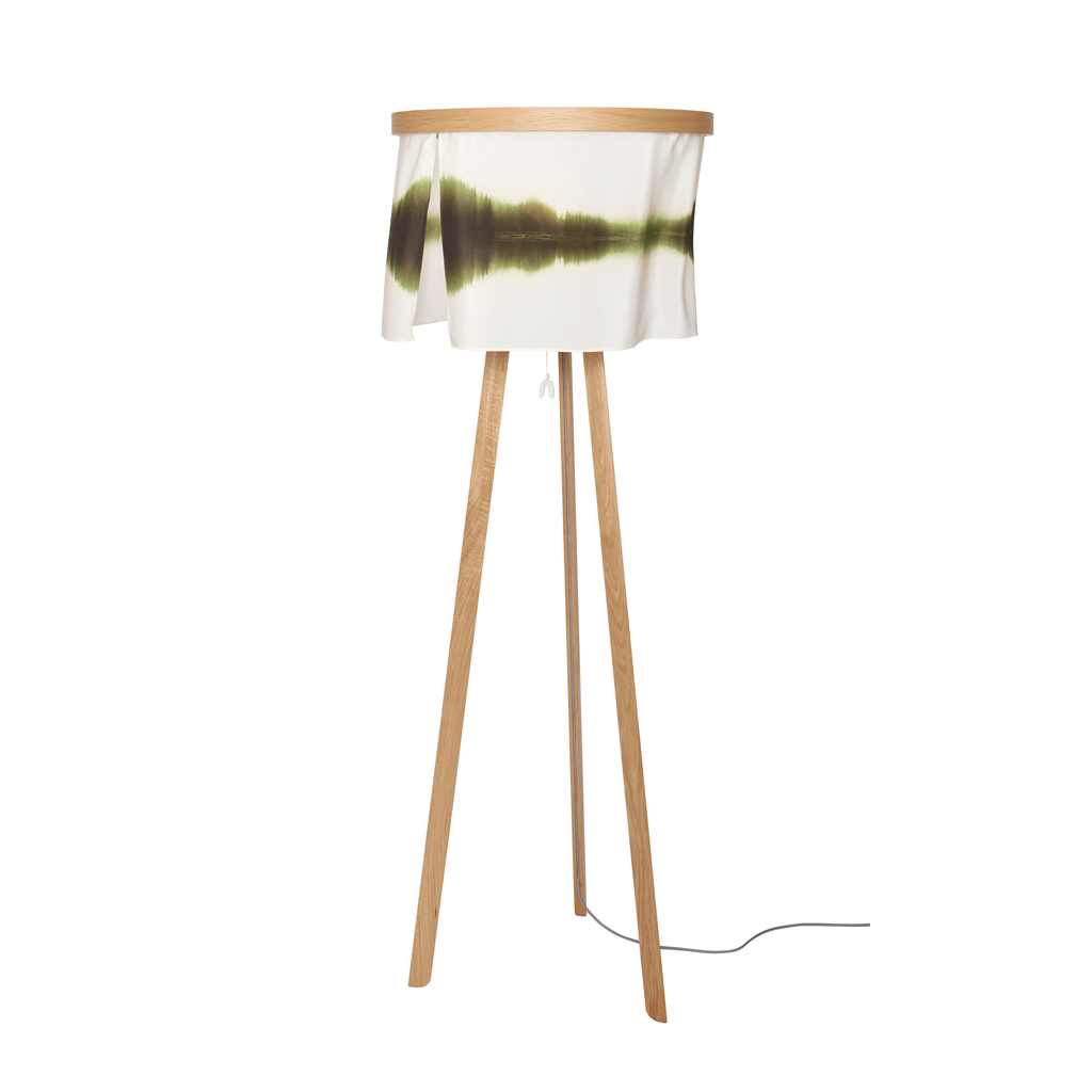 The Sognsvann floor lamp has a silk shade with an image of green trees reflected in the surface of the water of Lake Sognsvann in Norway. The shade is supported by a an elegant tripod of solid oak wood.